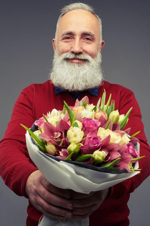 Homme mûr avec du charme offrant un bouquet des tulipes photo libre de droits