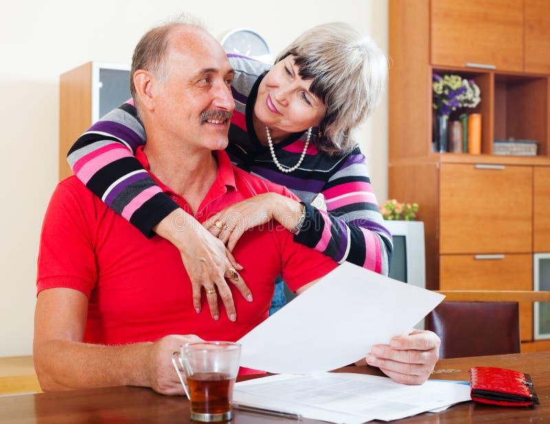 Homme mûr avec l'épouse lisant les documents financiers image libre de droits