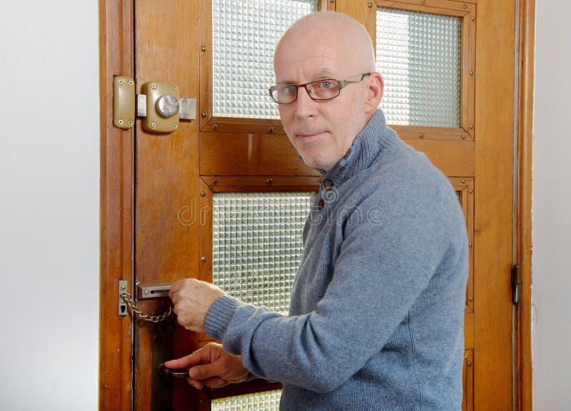 Homme mûr avec la fin bleue de pull la porte photographie stock