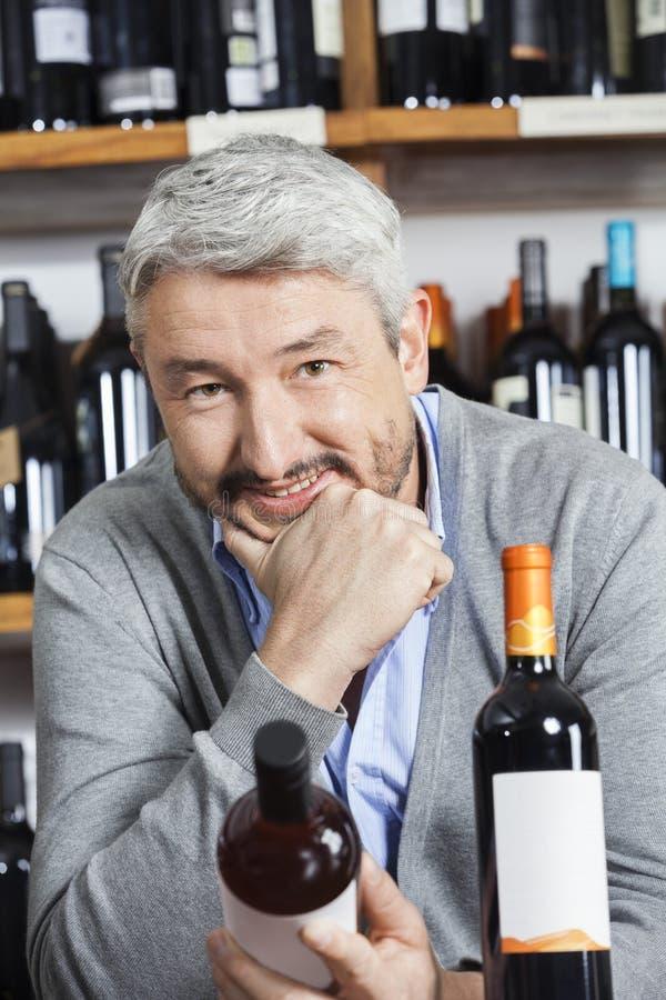 Homme mûr avec la main sur Chin Holding Wine Bottle photo stock