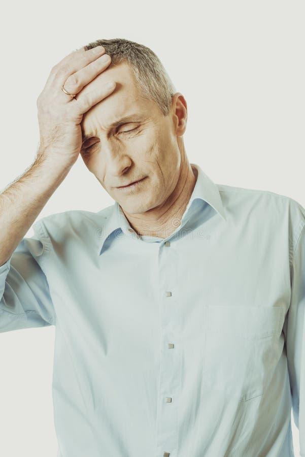 Homme mûr avec le mal de tête énorme image libre de droits