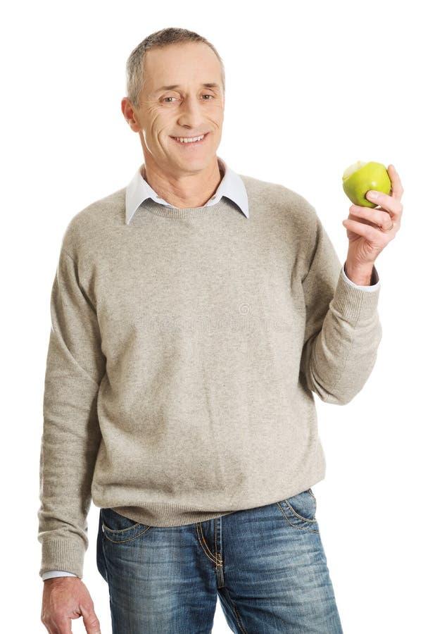 Homme mûr avec une pomme photographie stock libre de droits
