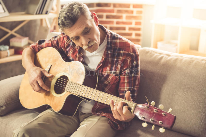 Homme mûr bel avec la guitare images stock