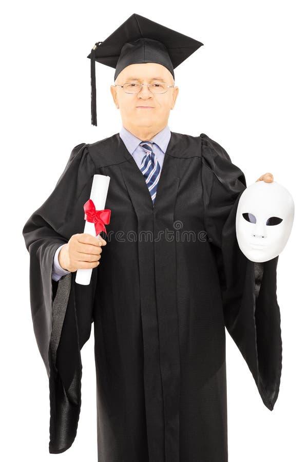 Homme mûr dans la robe d'obtention du diplôme tenant le masque de diplôme et de théâtre image libre de droits