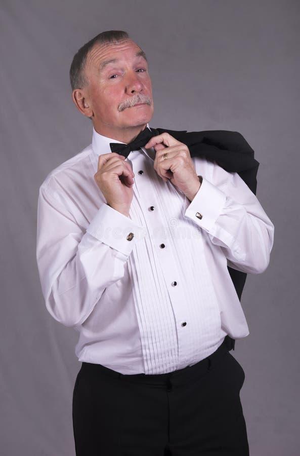 Homme mûr dans un costume fixant son noeud papillon, tenant une veste de dîner photo libre de droits