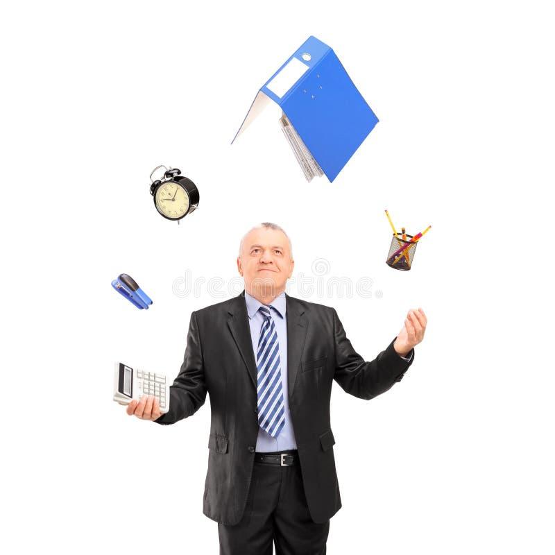 Homme mûr dans un costume jonglant avec des fournitures de bureau images stock