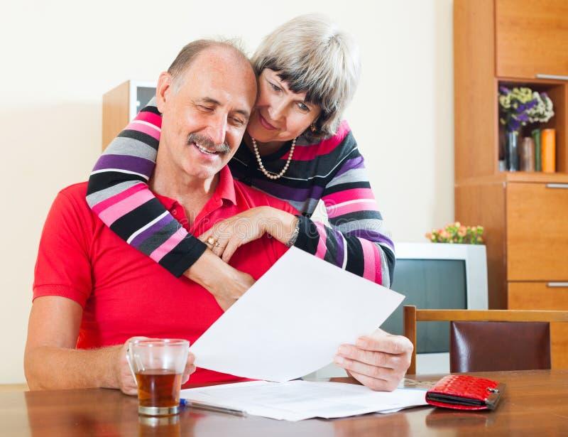 Homme mûr de Cheeful avec des documents de lecture d'épouse photographie stock libre de droits