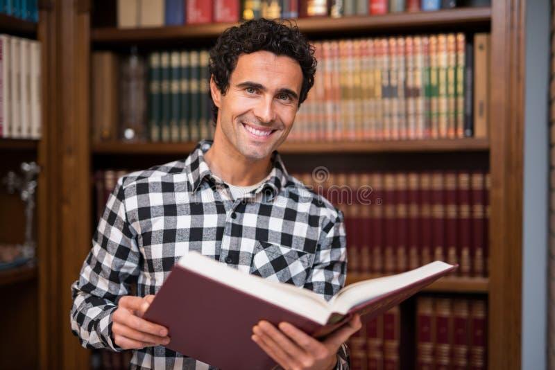 Homme mûr de sourire dans une bibliothèque image stock