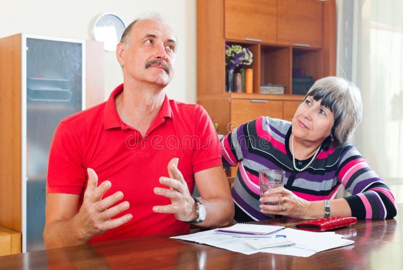 Homme mûr et femme ayant des problèmes financiers photos stock