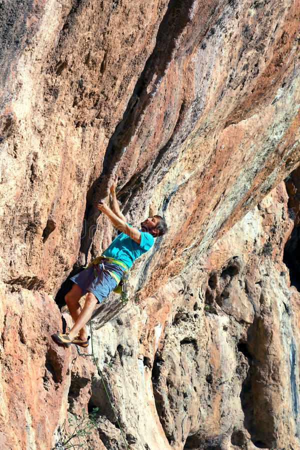 Homme mûr faisant la formation d'escalade sur la haute roche surplombante images stock