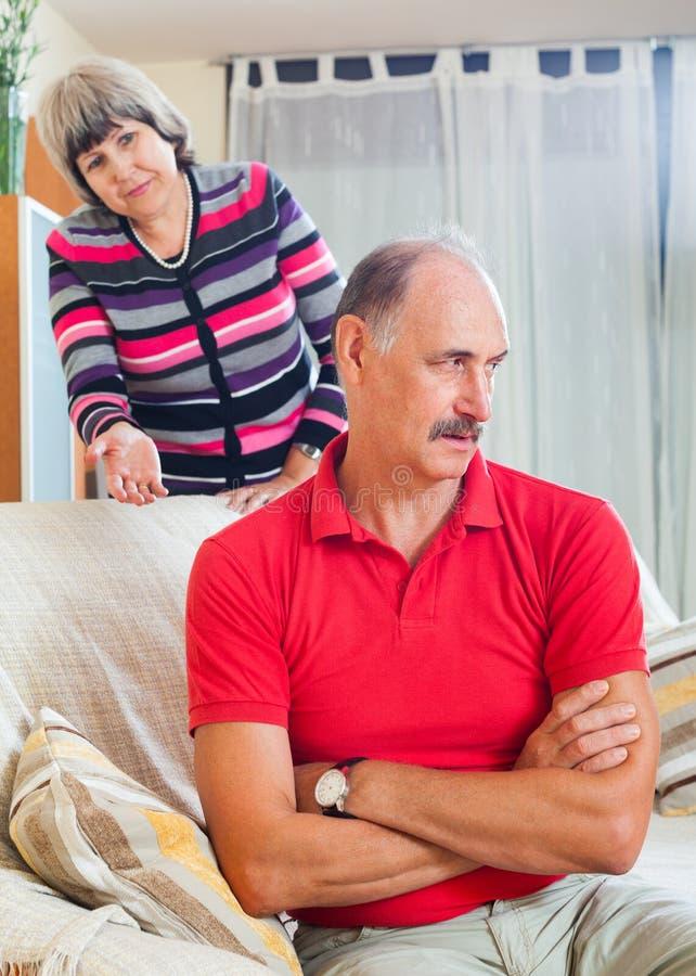 Homme mûr fatigué écoutant l'épouse fâchée photo libre de droits