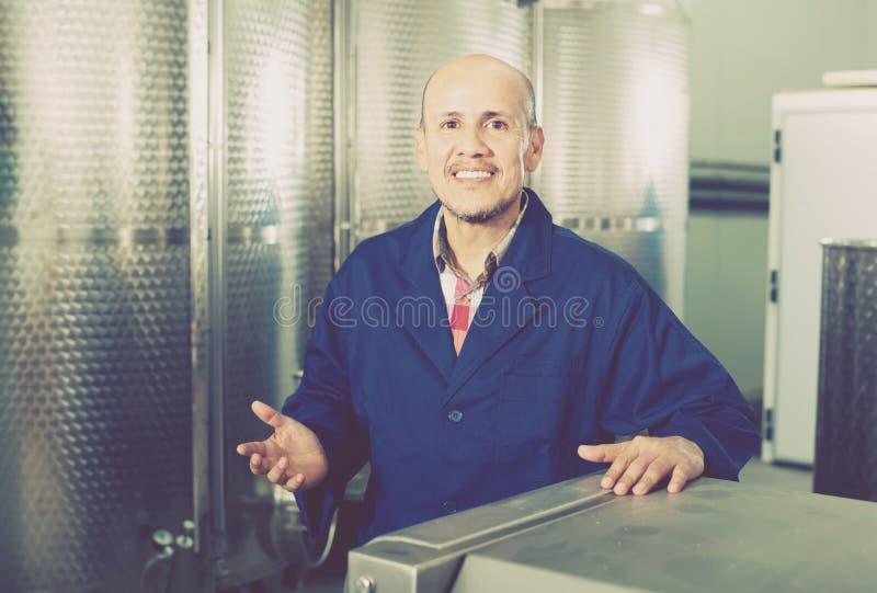 Homme mûr gai travaillant dans le secti secondaire de fermentation de vin photo libre de droits