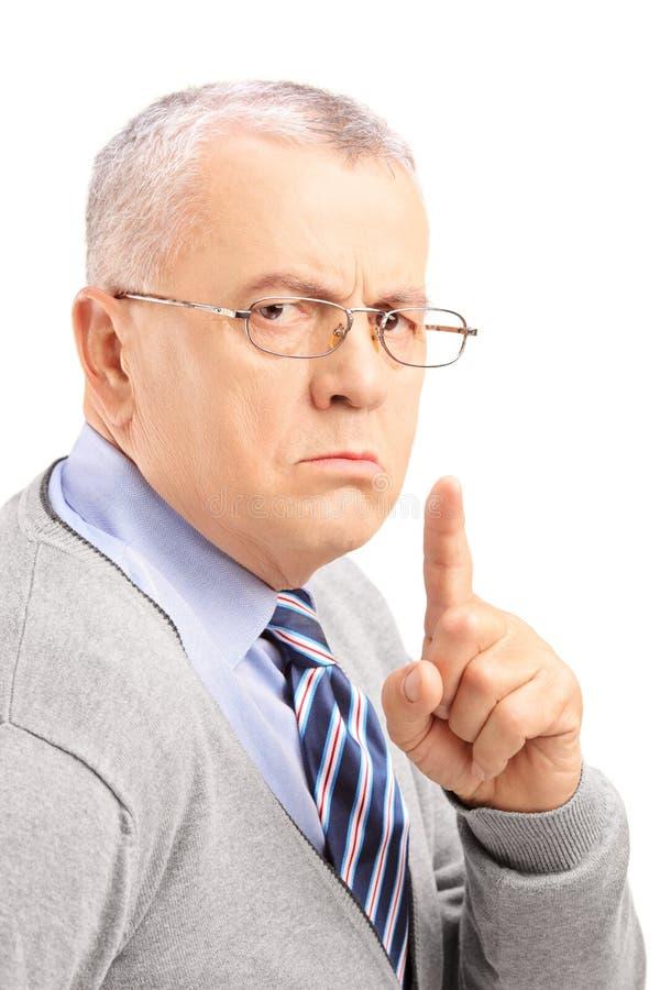 Homme mûr grincheux faisant des gestes le silence avec un doigt image libre de droits