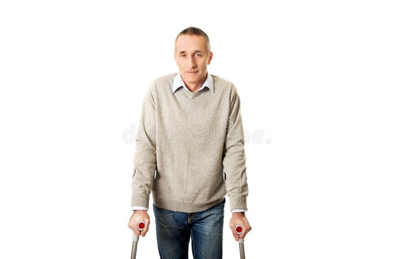 Homme mûr handicapé avec des béquilles image libre de droits