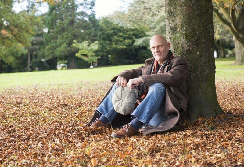 Homme mûr heureux s'asseyant sous un arbre en automne photo libre de droits