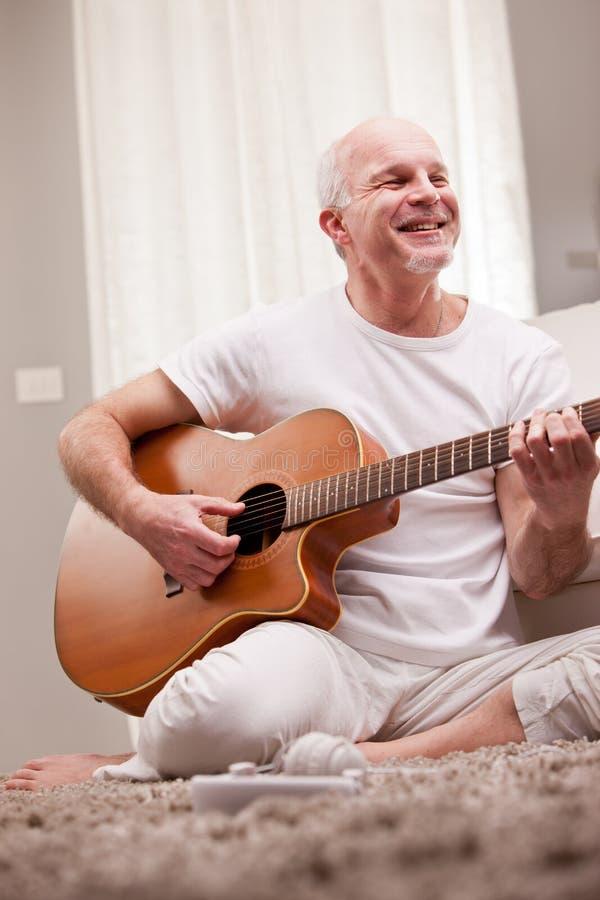 Homme mûr jouant la guitare à la maison photos libres de droits