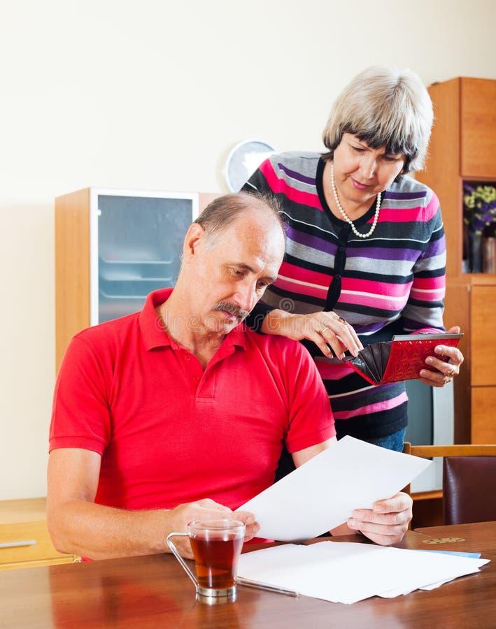 Homme mûr sérieux avec l'épouse lisant les documents financiers photos stock