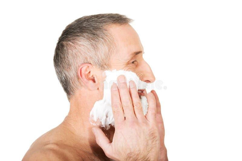 Homme mûr s'appliquant rasant la mousse images stock