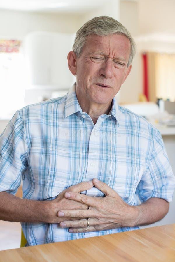 Homme mûr souffrant de la douleur abdominale à la maison images libres de droits