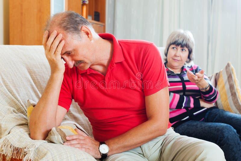 Homme mûr triste écoutant l'épouse fâchée photographie stock libre de droits