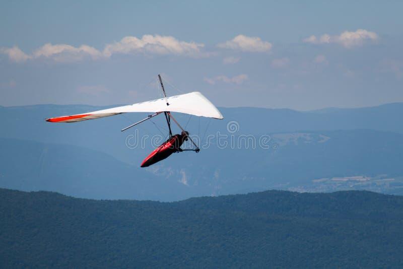 Homme Main-glissant en mi ciel au-dessus de Mointains un jour chaud d'été photo libre de droits