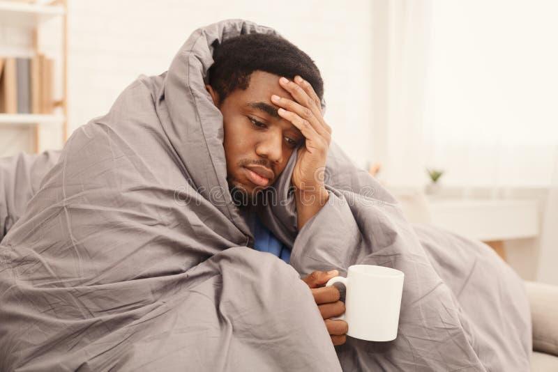 Homme malade d'afro-américain buvant du thé curatif chaud photos stock