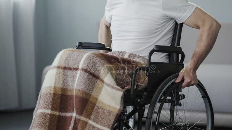 Homme malade dans le fauteuil roulant recueillant la force, décidant d'avancer, puissance de volonté photos libres de droits