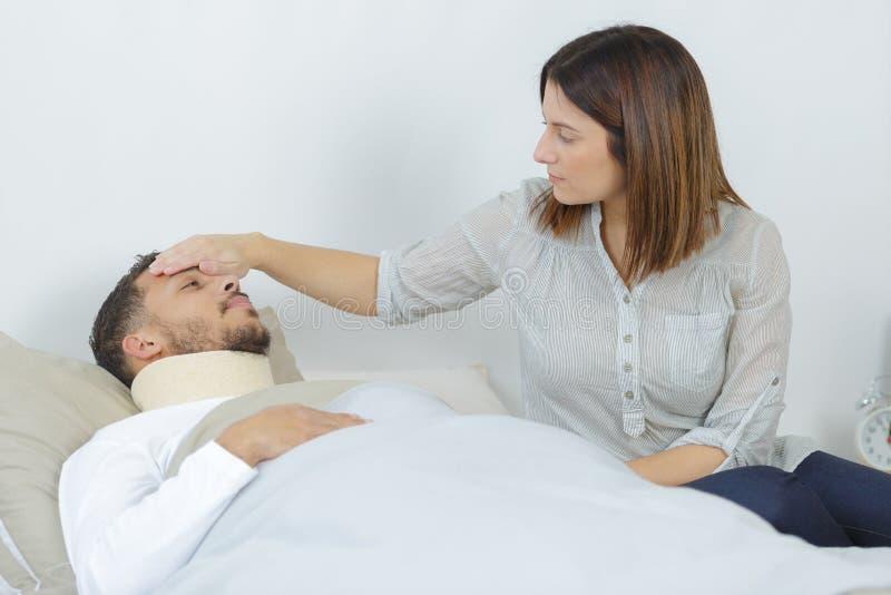 Homme malade se situant dans le lit à l'hôpital et à l'épouse photographie stock