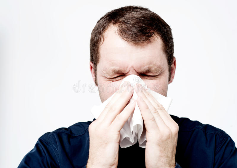 Homme malade soufflant son nez photographie stock libre de droits