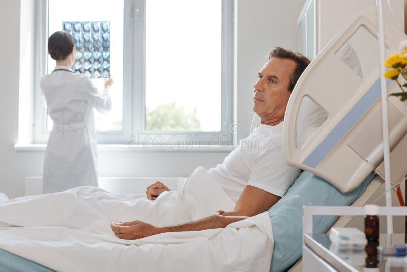 Homme malheureux déprimé se trouvant sur le lit d'hôpital images stock