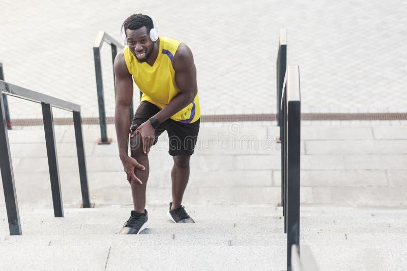 Homme malheureux de portrait Problèmes avec des joints dans les athlètes après essai images stock