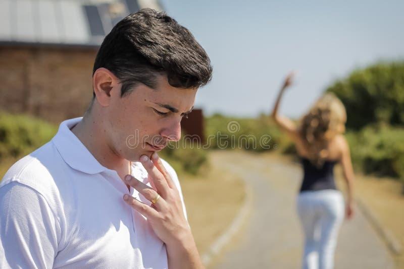 Homme malheureux et femme fâchée partant après querelle photographie stock