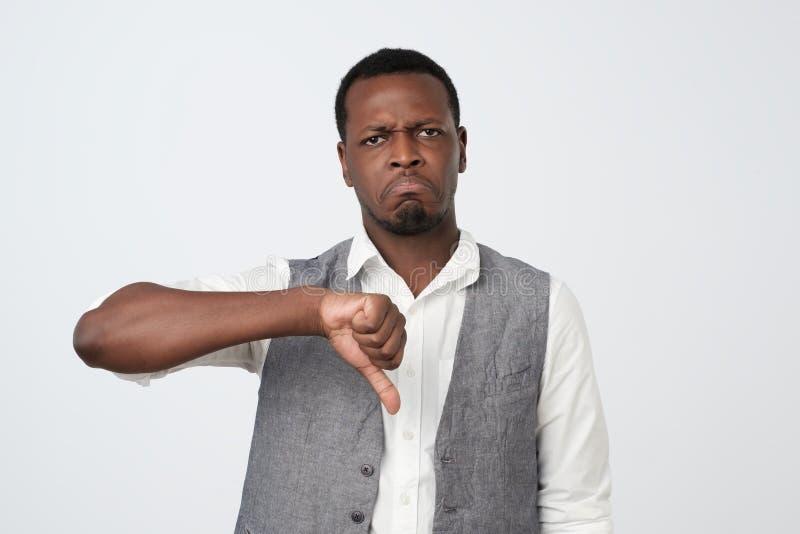 Homme malheureux, fâché, fou et grincheux donnant des pouces en bas de geste image stock
