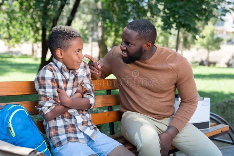 Homme malheureux sombre ayant un entretien avec son fils photographie stock