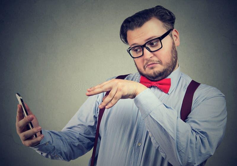 Homme manoeuvrant avec le smarpthone et faire des gestes photo stock