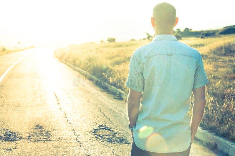 Homme marchant dans le coucher du soleil sur la route vide photo stock