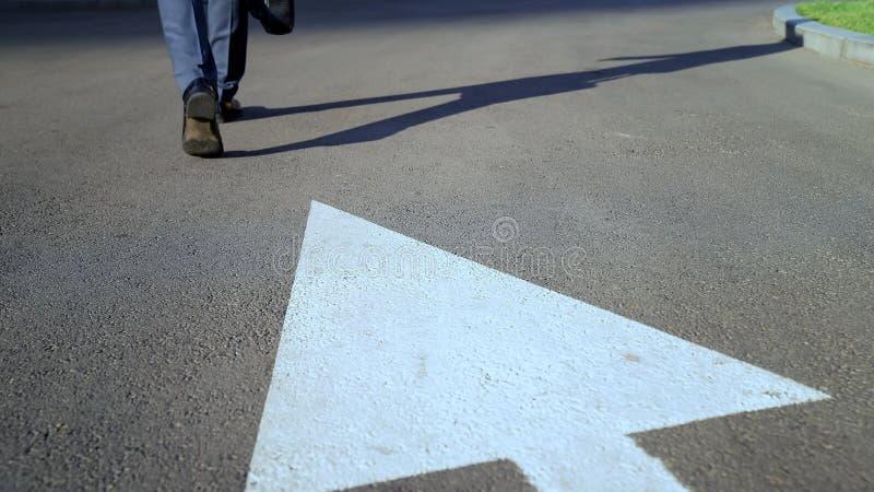 Homme marchant le long de la flèche blanche, concept de choisir la manière de propre droit dans la vie, carrière image libre de droits