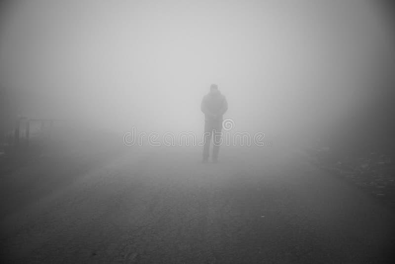 Homme marchant loin sur la route brumeuse Seul équipez debout sur la route goudronnée brumeuse et brumeuse rurale image libre de droits