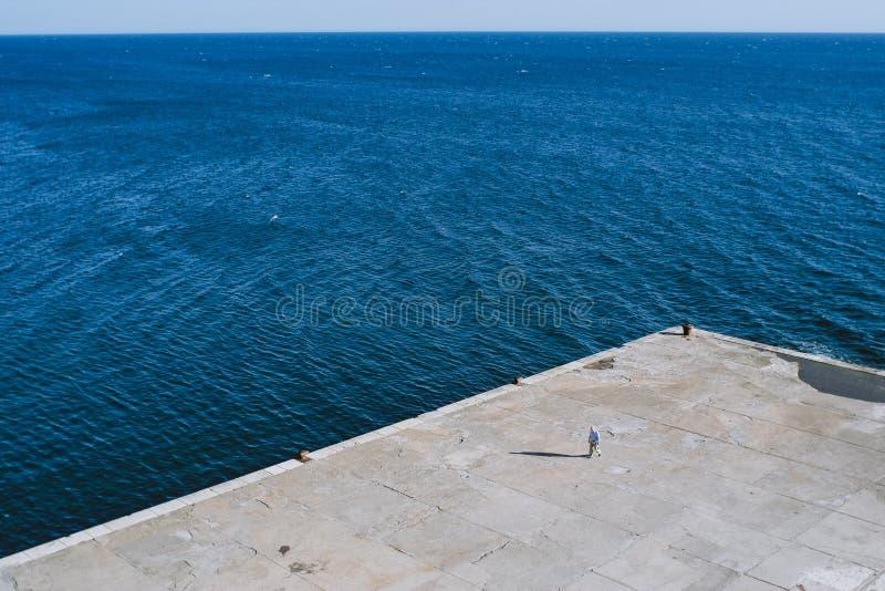 Homme marchant sur un dock concret sur la côte de la Mer Adriatique dans Ulcinj, Monténégro photos stock