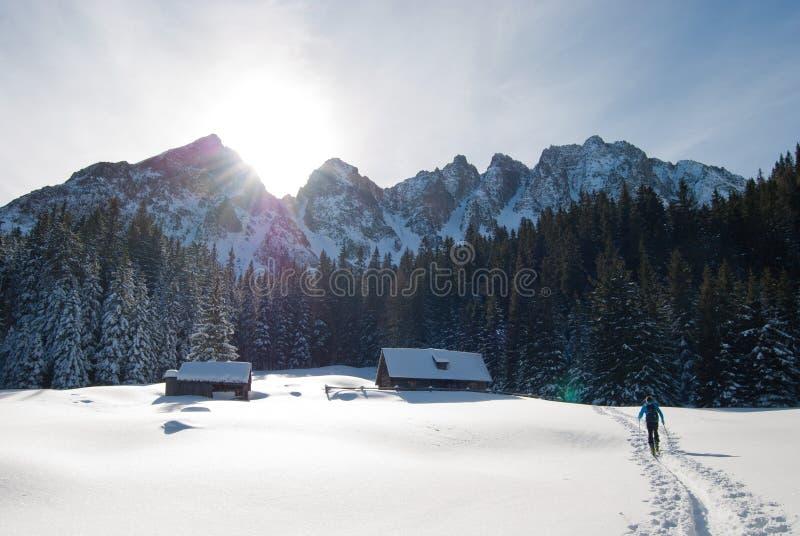 Homme marchant vers Brown Housen dans un endroit de neige photos stock