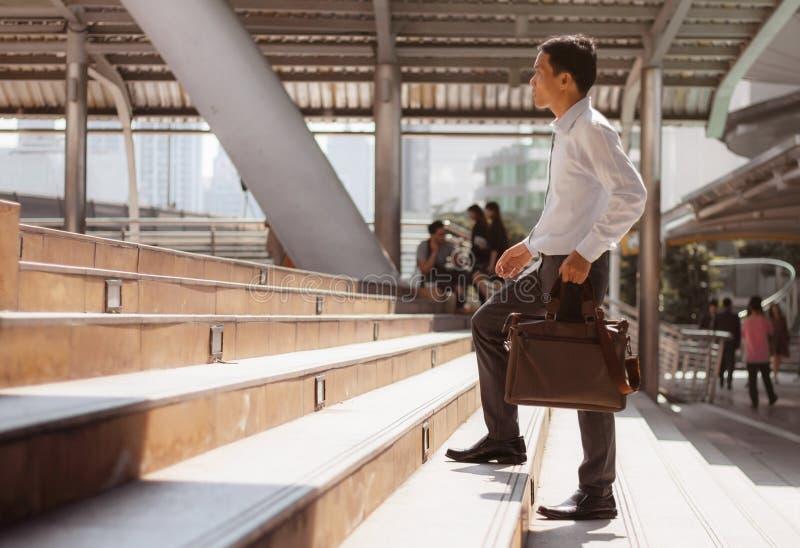 Homme marchant vers le haut de l'escalier photographie stock