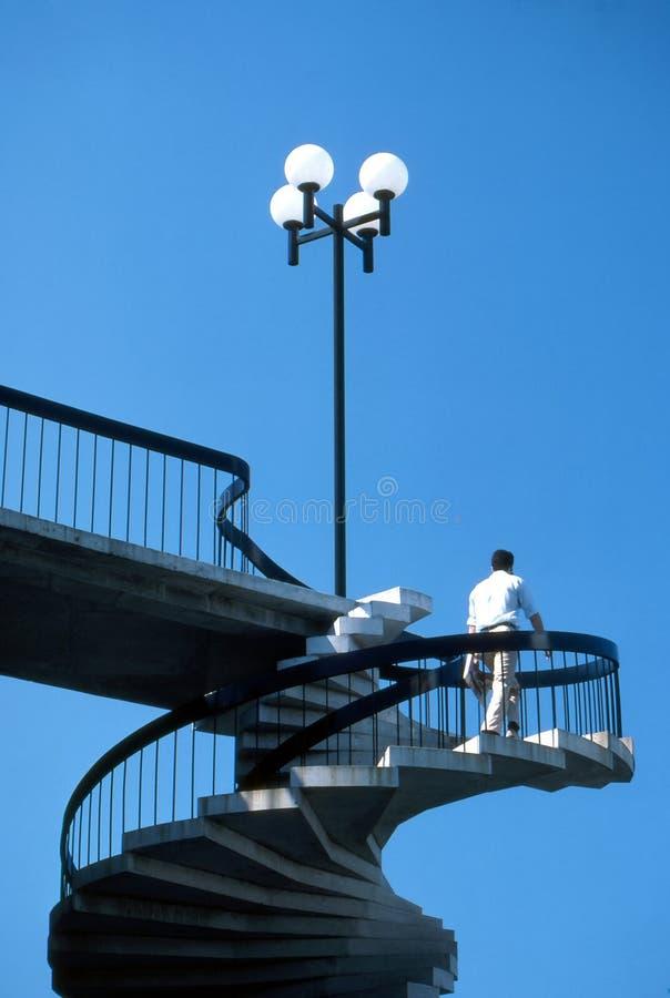 Homme marchant vers le haut de tordre des escaliers images libres de droits