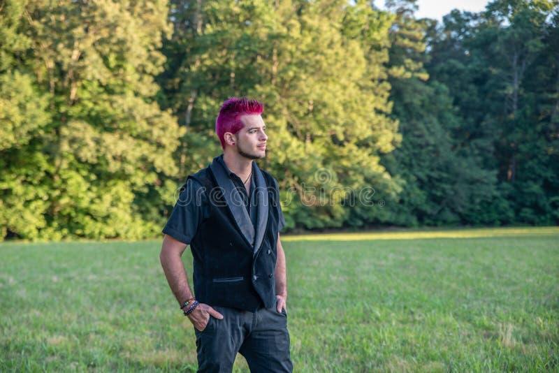 Homme masculin blanc alternatif avec les cheveux roses regardant fixement dans la distance, contemplative image stock
