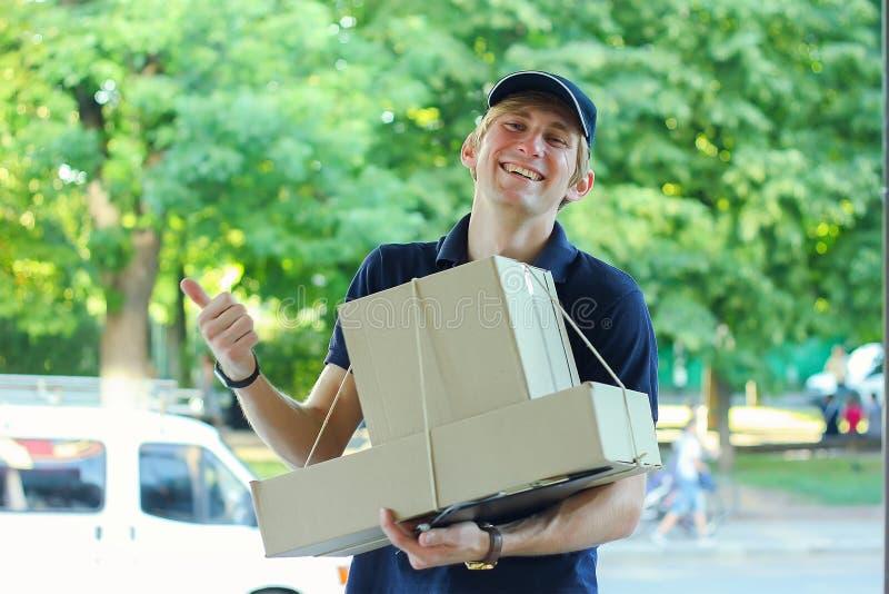 Homme masculin de sourire de messager de la livraison postale dehors photographie stock libre de droits