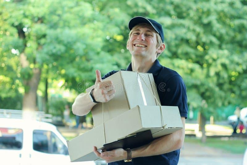 Homme masculin de sourire de messager de la livraison postale dehors images stock