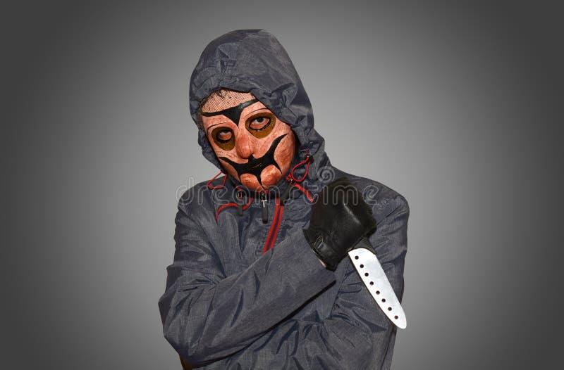 Homme masqué avec un couteau photographie stock libre de droits