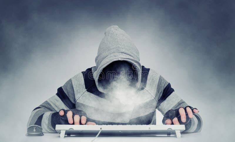 Homme mauvais de pirate informatique anonyme dans le hoodie derrière le clavier, fumée au lieu de visage images libres de droits