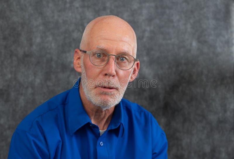Homme mauvais, portrait d'un homme avec les lèvres pincées regardant directement dans la caméra image libre de droits