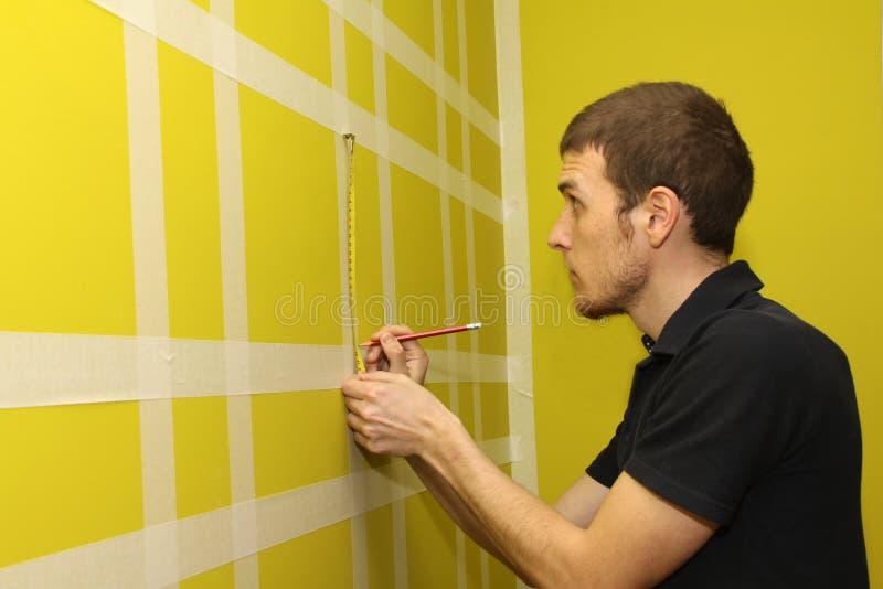 Homme mesurant le mur intérieur images libres de droits