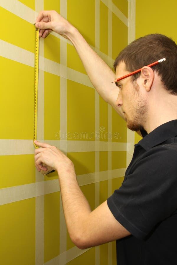 Homme mesurant le mur intérieur photographie stock libre de droits